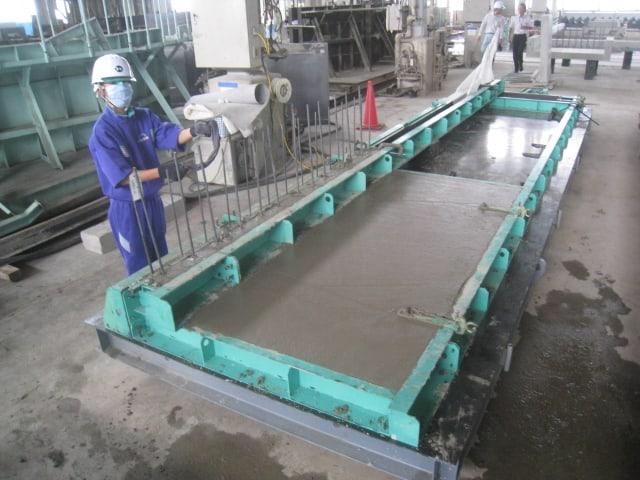 汚れた鉄筋の掃除の様子 コンクリート工場において