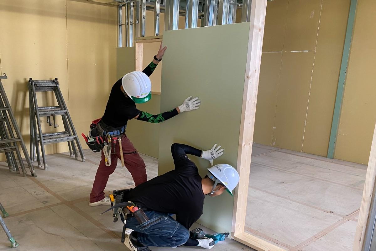 ボード仕上げ工事 自社練習倉庫での壁貼り練習風景